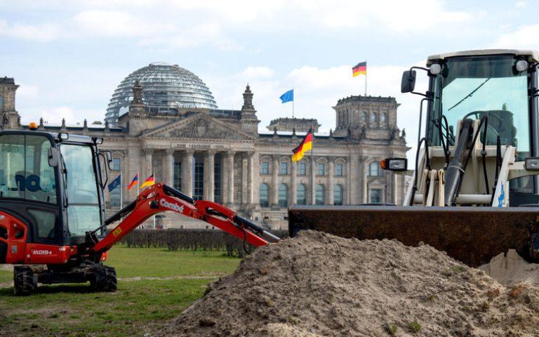 ARCHIV - 20.03.2019, Berlin: Zwei Bagger stehen auf dem Rasen vor dem Reichstagsgebäude. (zu dpa «Rasenfläche vor Reichstag demnächst wieder frei») Foto: Monika Skolimowska/zb/dpa +++ dpa-Bildfunk +++