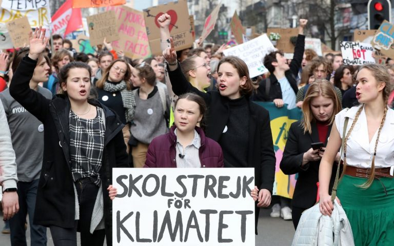 16-year-old Swedish environmental activist Greta Thunberg and Anuna De Wever, a Belgian climate student activist take part in a protest claiming for urgent measures to combat climate, in central Brussels, Belgium February 21, 2019. The placard reads: